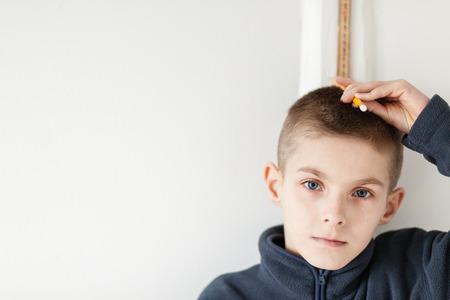 ハンサムな少年は、彼の高さ間探してまっすぐにカメラをチェックする測定棒で壁に立っています。左側にコピー スペースを強調しています。