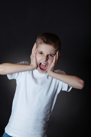 ire: Half Body Shot of an Irritated Young Boy in White Casual Shirt, Shouting at Camera with Hands on his Face Against Black Background.