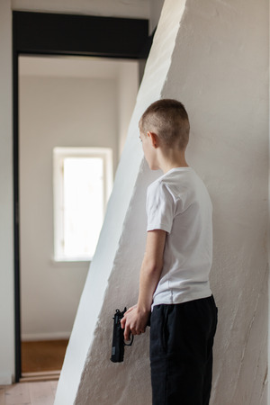 aggressor: Young Boy Holding a Gun, Hiding Behind the Wall While Waiting Someone to Come Inside the House. Stock Photo