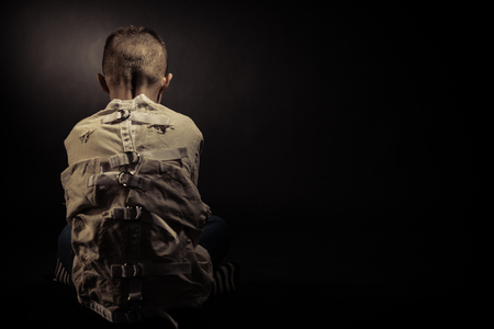 Rear View of a Lonely Poor Young Boy Seated on the Floor in an Isolation Unit Against Black Background with Text Space.