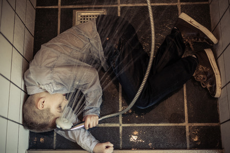 intoxicated: High Angle View of a Sick Young Boy Collapsed Inside the Rest Room While Holding a Shower Head. Stock Photo