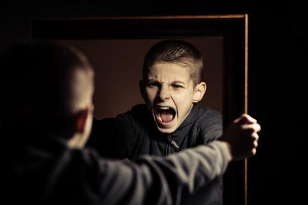 Close up Giovane ragazzo arrabbiato grida sul proprio riflesso specchio con la bocca spalancata su sfondo nero.