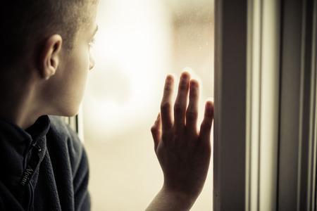 Bliska Lonely Sierota Chłopiec w sierocińcu patrząc na zewnątrz trzymając szybą.