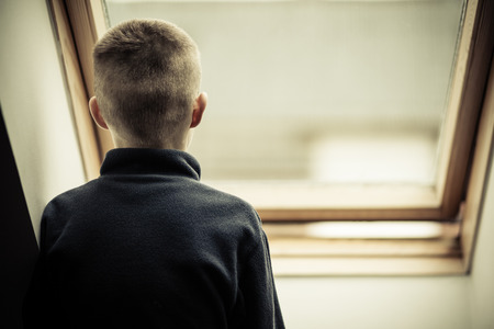 envious: Close up Rear View of a Lonely Young Boy Looking Outside View Through Glass Window at Home.