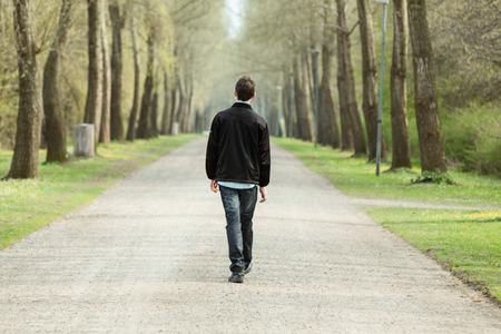Teenage boy walking away from the camera down a rural road lined with trees on a misty cold day