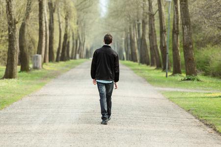 Teenage jongen lopen weg van de camera in een landelijke weg omzoomd met bomen op een mistige koude dag Stockfoto