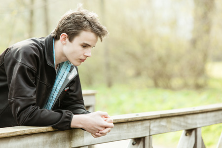 downwards: Thoughtful attractive young teenage boy leaning on a wooden railing outdoors staring downwards in deep contemplation