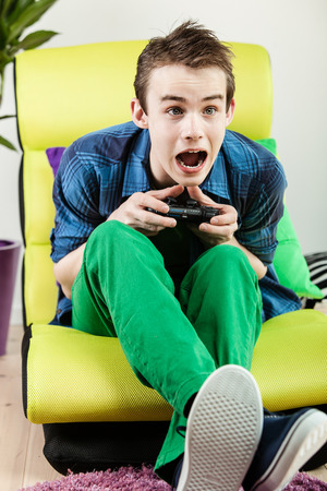 exuberant: Exuberant male teenager in green pants screaming while sitting in yellow chair playing video game Stock Photo