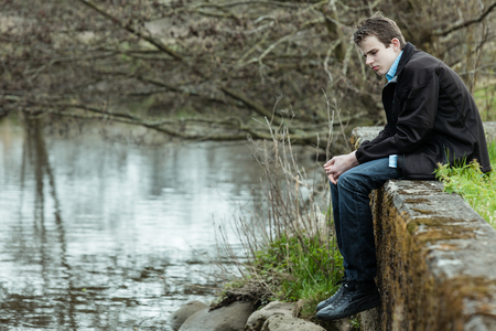 alone boy: Lonely young teenage boy sitting on a wall above a lake or river staring down into the water with a serious expression, side view