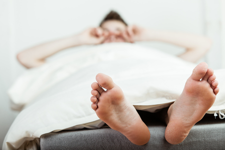 Young boy waking up in the morning rubbing his eyes with a view of his bare feet in the foreground protruding from under the duvet Stock Photo