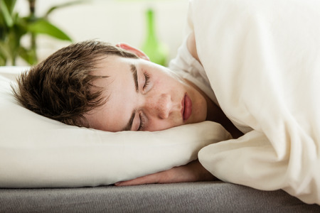 Young boy enjoying a peaceful sleep in his bed, close up head and shoulders with neutral off white bedclothes