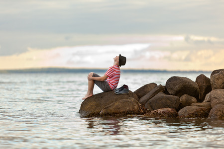 boy sitting: Young man enjoying an ocean sunset sitting barefoot on rocks at the edge of the sea wearing a trendy hat looking up into the air, side view with copy space