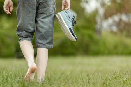 low angle view: Young man carrying his shoes walking barefoot across a grassy field , low angle view of his legs