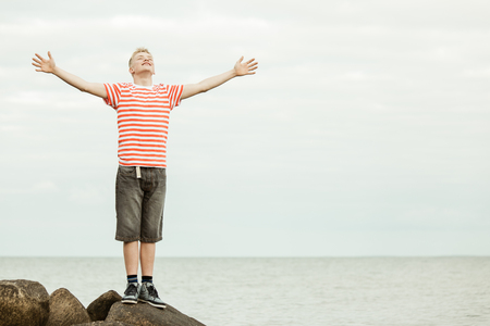 short haired: Single young short haired teenager in striped shirt with big smile and wide open arms standing on large rocks near water with copy space