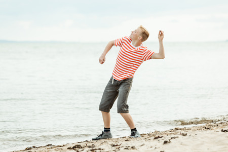 Teenage boy throwing stones into the ocean as he stands on the sandy beach in his clothes while enjoying his summer vacation