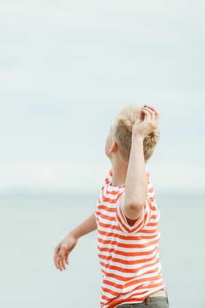view from behind: View from behind of a young teenage boy tossing stones into the sea on his summer vacation Stock Photo