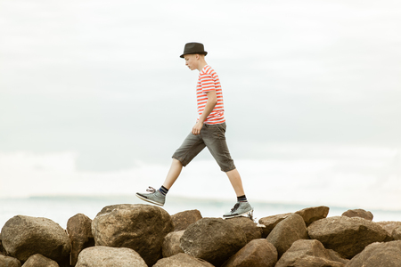 Teenage boy striding across rocks at the seaside in a trendy summer outfit, side view against an ocean backdrop