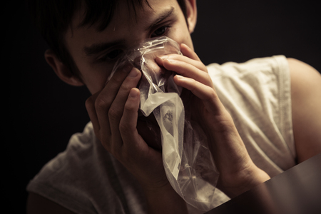 inhaling: Close up of single male teenager inhaling narcotics from plastic re-sealable bag on his mouth