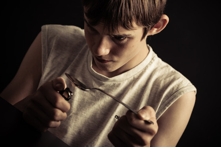 druggie: Single drug addicted sleeveless male teenager lighting spoon full of narcotics with cigarette lighter Stock Photo