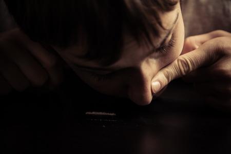 abuso: Primer plano de adolescente masculino que pone el dedo en el orificio nasal mientras esnifa coca�na l�neas en la mesa