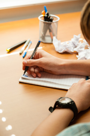 person writing: Over the shoulder view of unidentifiable young person wearing watch and writing on note pad next to crumpled up pieces of paper Stock Photo