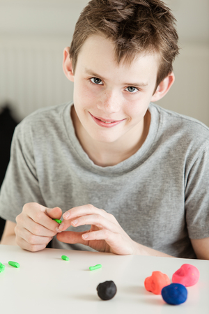 short sleeve: Single smiling boy in gray short sleeve shirt forming small bits of clay from larger pieces on white table