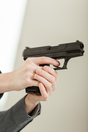youth crime: Bare Hands Holding a Firearm and Pointing Away From Camera, Ready to Shoot.