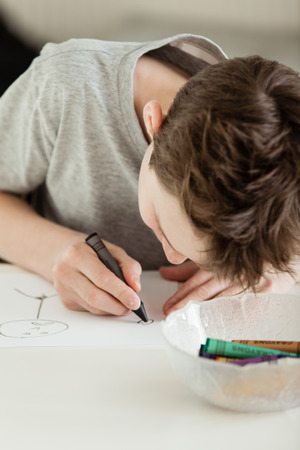 sketchpad: Single boy in gray short sleeve shirt looking down carefully at paper next to bowl of other colors as he draws figures with a black crayon