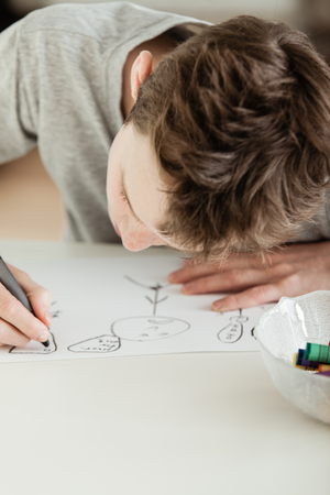 sketchpad: Close up Serious Teenage Boy Draw Something on White Paper at the Table