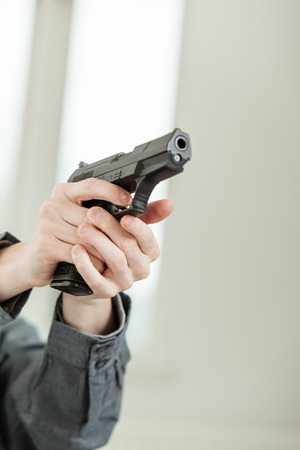 felon: Hand of a Young Boy Holding a Real Hand Gun Pointing Away at the Camera Stock Photo