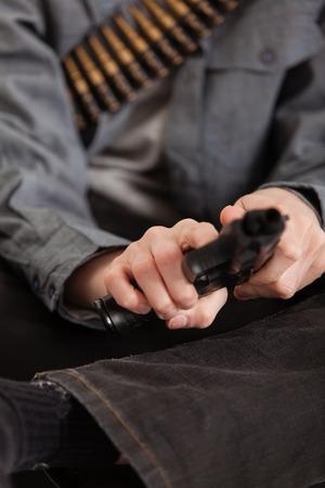 hoodlum: Close up Bare Hands of a Young Boy Cocking a Real Hand Gun.