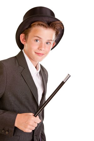 pert: Cute young boy dressed as a magician in a top hat and jacket waving a wand in his hand, upper body isolated on white Stock Photo
