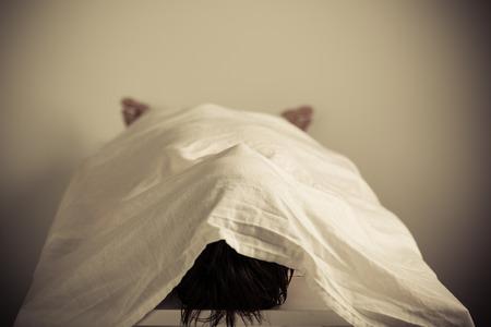 Corpse d'une personne allongée sur la table à l'intérieur d'un Morgue avec Blanc Cloth Cover.
