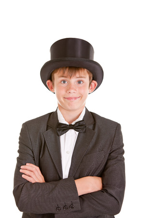 jaunty: Dapper confident young boy in a top hat, bow tie and black jacket standing grinning at the camera with folded arms, isolated on white