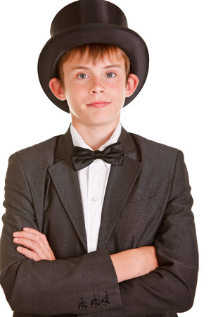 jaunty: Half Body Shot of an Elegant Young Boy Wearing Formal Suit with Top Hat, Crossing his Arms Over his Chest and Looking at the Camera with Half Smile Face. Isolated on White.