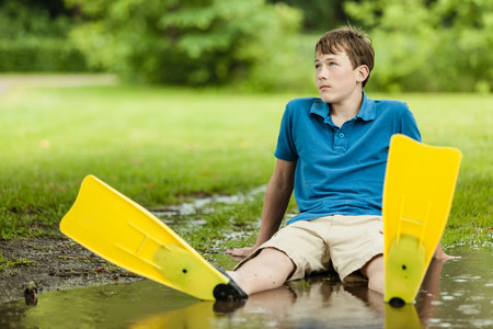 yearning: Daydreaming male teenager wearing shorts and diving fins sitting back in large backyard puddle