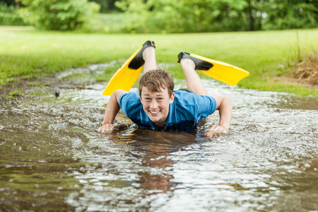 he laughs: Happy teenager in diving fins laughs as he tries to swim in large shallow muddy backyard puddle