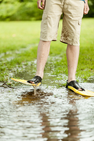 unidentifiable: Unidentifiable person in shorts and diving flippers splashing in large puddle on turf grass