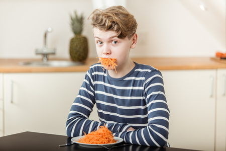 mouthful: Waist Up of Boy with Wavy Blond Hair Sitting at Kitchen Table with Plate and Mouthful of Shredded Carrots and Looking Surprised - Humorous Nutrition Concept Image Stock Photo