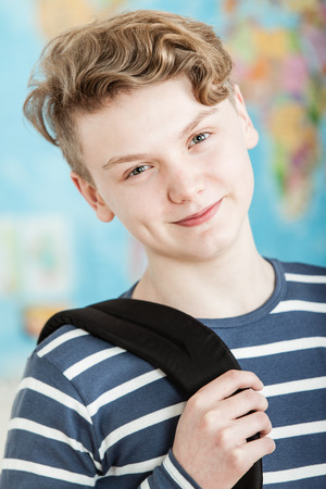 knapsack: Head and Shoulders Portrait of Smiling Boy with Wavy Blond Hair Standing in Classroom with World Map in Background, Wearing Blue and White Striped Shirt and Holding Knapsack