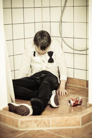 Bebido joven adolescente durmiendo en una ducha apoyado contra las baldosas en su ropa con una lata vacía de bebidas junto