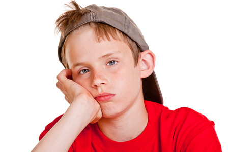 surly: Bored depressed young boy with sad lonely eyes resting his chin on his hand looking at the camera with a doleful expression