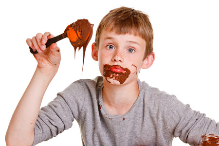 face covered: Baking time with a young boy eating the melted chocolate covering his mouth and chin holding up a dripping wooden spoon with big innocent eyes Stock Photo
