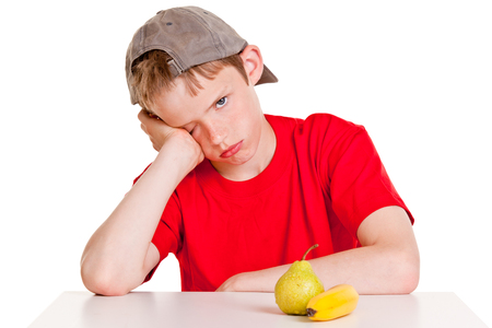 unmotivated: Single young boy in red shirt, backward hat and hand on cheek with bored expression sitting in front of green pear and yellow banana over white background