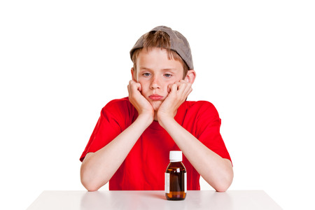 surly: Single pouting boy in red short sleeved shirt and backwards hat with hands on cheeks next to medicine bottle