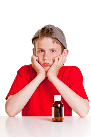 surly: Single sulking teenager in red short sleeved shirt and backwards hat with hands on cheeks next to medicine bottle