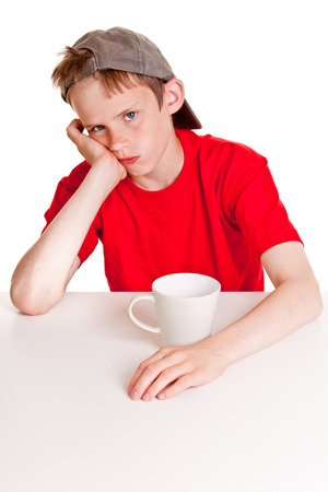 morose: Single pouting young boy in red shirt, backward hat and hand on cheek with bored expression sitting in front of large white mug over blank background
