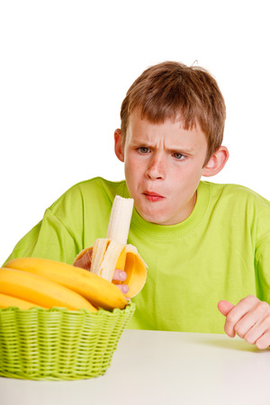 unimpressed: Unimpressed young boy eating a fresh banana with a look of horror on his face as he chews the first mouthful while seated at the table