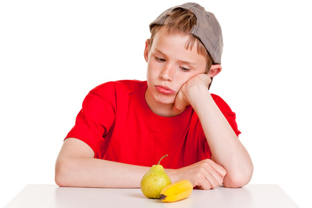 surly: Morose young boy sitting at a table staring at a ripe banana and pear with a glum expression, conceptual of a healthy diet