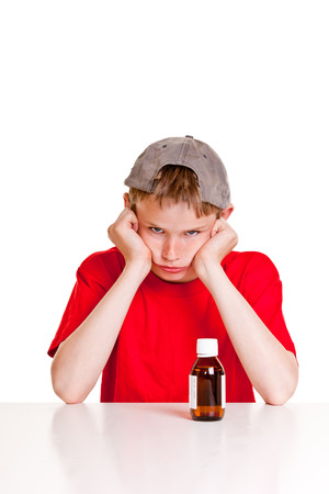 glowering: Single angry teenager in red short sleeved shirt and backwards hat with hands on cheeks behind medicine bottle